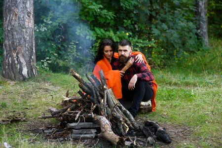 Couple in love at picnic with fire in forest, trees