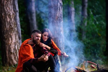 Young couple roast sausages on stick on bonfire in forest.