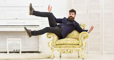 Macho attractive and elegant on cheerful face and happy expression. Playful mood concept. Man with beard and mustache wearing fashionable classic suit, sits, jumps on old fashioned armchair