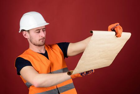 Foreman concept. Engineer, architect, builder on strict face holds blueprint in hands, supervises construction site. Male contractor with house plans wearing hard hat, controls works, red background.