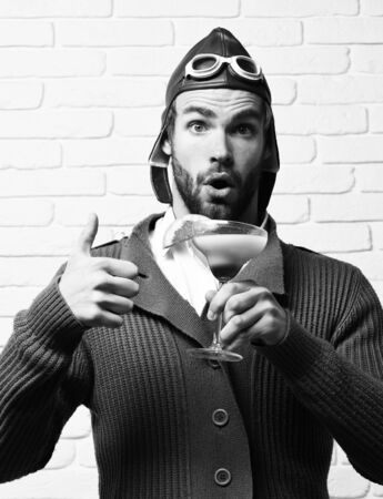 bearded pilot with cocktail in glass on white brick wall background 免版税图像