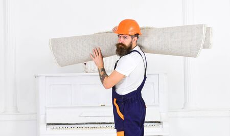 Relocating concept. Man with beard, worker in overalls and helmet carries rolled carpet, white background. Loader wrapped carpet into roll. Courier delivers furniture in case of move out, relocation. Standard-Bild