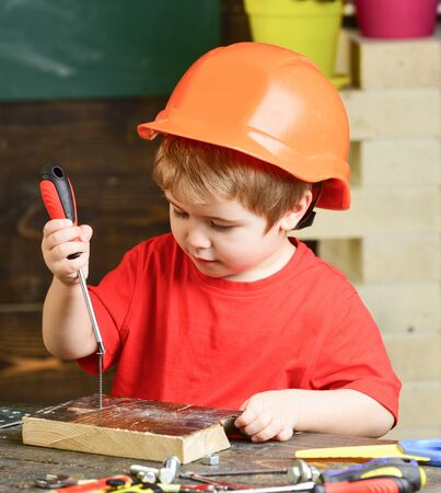 Kid boy in orange hard hat or helmet, study room background. Child dreaming about future career in architecture or building. Boy play as builder or repairer, work with tools. Childhood concept.