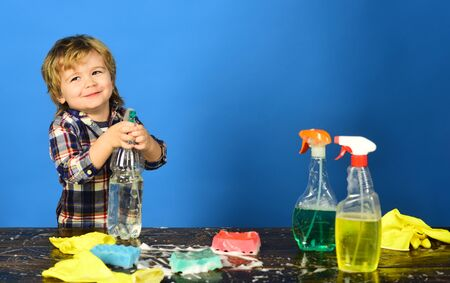 Cleaning activities concept. Child near table with cleaning supplies on.