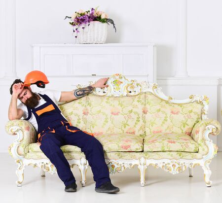 Loader sit on sofa, having rest. Man with beard, worker in overalls and helmet sits on couch tired, white background. Exhausted loader concept. Courier relaxing while moving furniture, relocation. 版權商用圖片