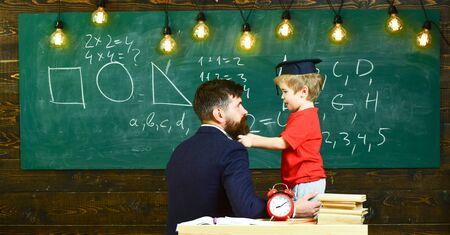 Young male teacher guides his child student to learning while speaking, sitting in classroom, chalkboard with scribbles on backgraund, rear view. 版權商用圖片