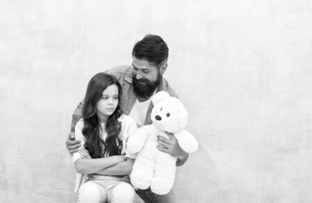 Look at this toy. Father show soft toy to little daughter. Upset child and bearded man with toy bear. Game and play. Toy shop. Stay childish, copy space 版權商用圖片
