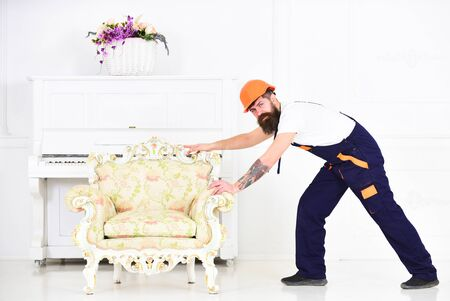 Delivery service concept. Courier delivers furniture in case of move out, relocation. Man with beard, worker in overalls and helmet pushes armchair, white background. Loader carries armchair.