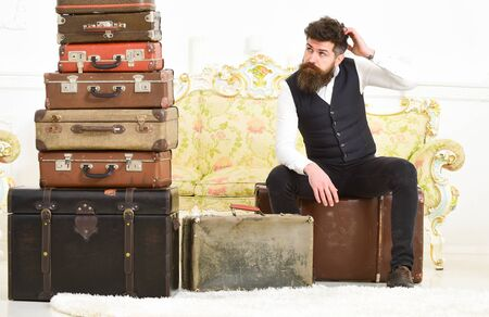 Luggage and relocation concept. Macho elegant on tired face sits, exhausted at end of packing, near pile of vintage suitcases. Man with beard and mustache packed luggage, white interior background. 版權商用圖片