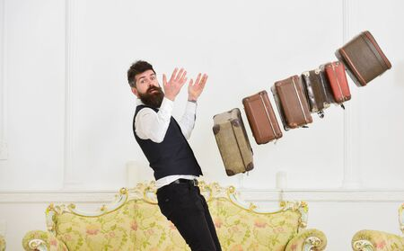 Baggage insurance concept. Porter, butler careless, dropping pile of vintage suitcases. Man with beard and mustache in classic suit delivers luggage, luxury white interior background