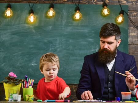 Family on busy faces creating, drawing. Teacher and kid in classroom with chalkboard on background. Father and son painting together in study room. Drawing lesson concept. 版權商用圖片