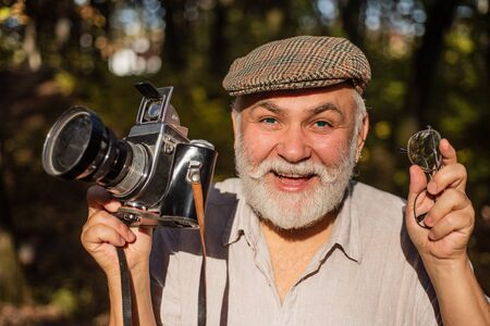 Hike with His Photography Equipment. Vintage and retro. Vintage Camera Photographer. senior photographer with camera. Lifestyle with nature. Travel Lifestyle vacations concept. Nature Photography Фото со стока