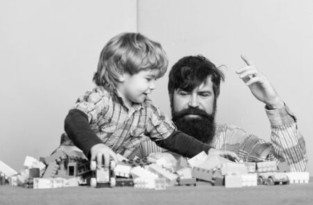 happy little boy with bearded man dad playing together. father and son play game. building home with colorful constructor. happy child development. happy family. leisure time. feeling happy