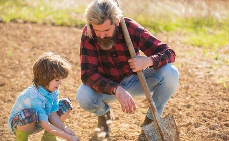 Where food comes from. Teaching son growing plants. Planting plants. Works in field. Father farmer instruct baby how to planting. Eco farming. Real skills. Dad with shovel and boy digging soil Banque d'images