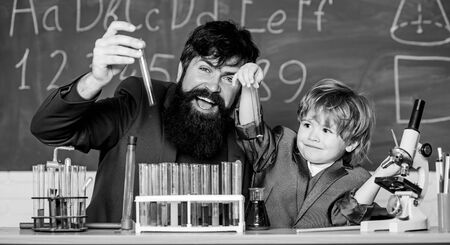 father and son child at school. bearded man teacher with little boy. Chemistry beaker experiment. Laboratory test tubes and flasks with liquids laboratory research and development. Responsibility.