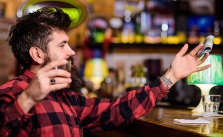 Alcohol addicted concept. Hipster holds glass with alcoholic drink Фото со стока