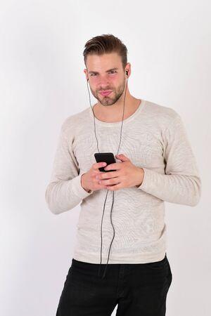 Macho with headphones listens to music. Guy with beard Фото со стока