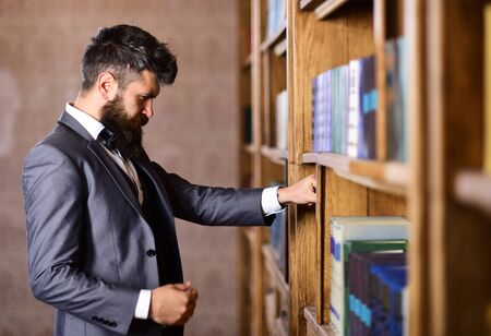 Librarian and profession concept. Librarian with long beard choose book.