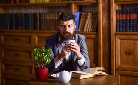Man with calm face enjoys hot beverage.