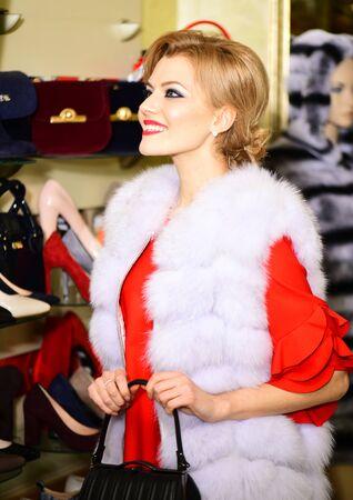 Lady wears fur coat with black handbag in boutique