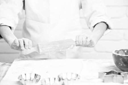 young male hands of cook chef in white uniform standing near table with rolling pin molds for cakes red bowl and lot of flour and cooking, on brick wall background