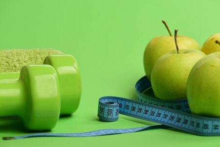 Sports and healthy regime equipment, copy space. Dumbbells in green color, rolled measure tape, towel and fruit on green background. Barbells near juicy green apples. Athletics and weight loss concept Stock Photo