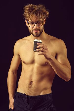 bearded sexy man holding coffee on black background