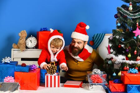 Santa and little assistant among gift boxes near Christmas tree Foto de archivo