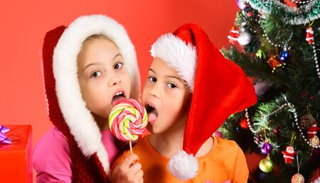 Children with happy faces share lollipop on red background. Banco de Imagens