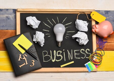 White lamp with paper, notebook, pen, chalk, piggy bank, numbers and elastics. Board with stationery on wooden background. Idea lamp with business accessories on grey chalkboard. Idea creation concept