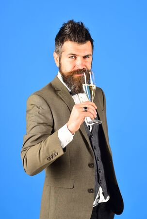 Businessman with intriguing happy face holds sparkling wine.