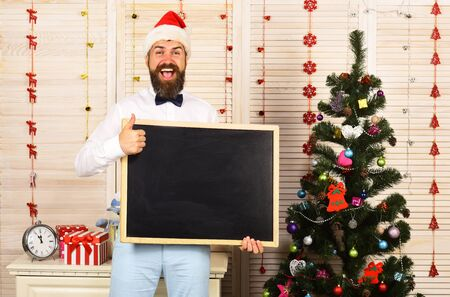 Man with beard holds blank blackboard, copy space. Banco de Imagens