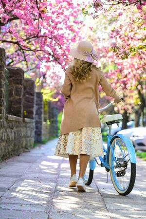relax in park. fashion and beauty. woman ride vintage bicycle. romantic girl under sakura blossom. beautiful spring season nature. cherry tree blooming flowers. pink blossoming sakura.