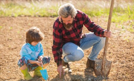 Growing plant. Father teach son to plant in soil. Bearded man and child set plant in spring. Open ground plant. Family use gardening tools. Hobby farm. Farming and agriculture.