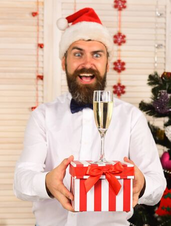 Man with beard holds striped present box with champagne glass.