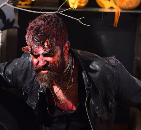 Devil or monster partying. Halloween costume party concept. Man wearing scary makeup with dark Halloween decor on background. Demon with horns, wild or evil face and dried blood on hair