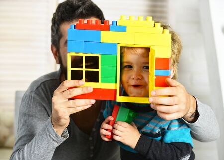 Dad and kid hide behind house wall made of blocks