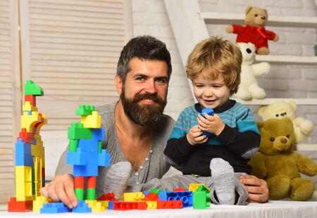 Father and son with smiling faces create colorful constructions
