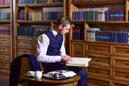 Professor with thoughtful face reads book in antique interior Banque d'images
