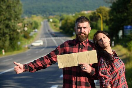 Adventure and hitchhiking concept. Couple with pensive faces