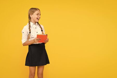 The joy of good knowledge. Cute small girl holding book on yellow background. Adorable little schoolchild getting knowledge from book. Knowledge and skills. Knowledge day or September 1, copy space Stock fotó