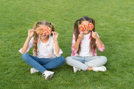 Not only sweet but gorgeous to look at. Little girls with sweet look on green grass. Happy children cover eyes with candies. Sweet treats. Candy shop. Sugar confectionery. Life is sweet, enjoy it all. 免版税图像