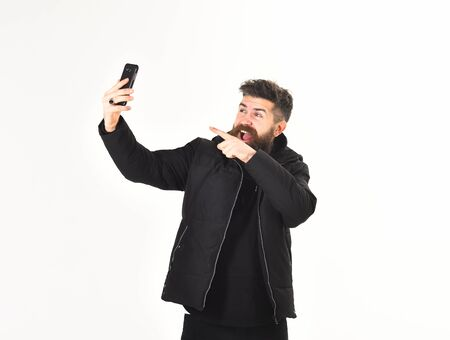 Blogger with beard makes selfie photo or streaming video. Stockfoto