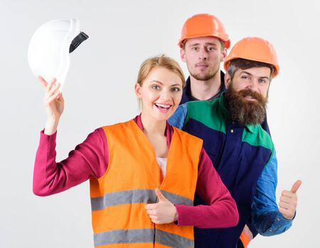 Woman and men holds hard hats. Cheerful collective concept.