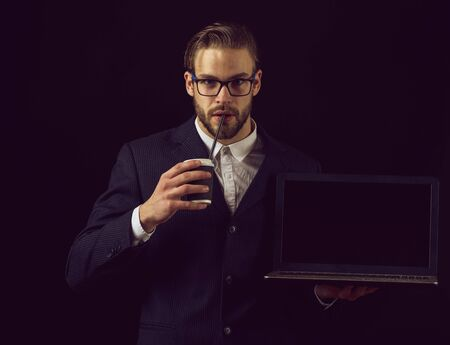 thoughtful business man in suit on black background, copy space Foto de archivo