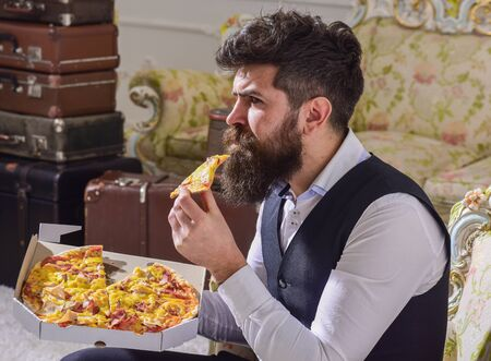 Man with beard and mustache holds delivered box with tasty fresh hot pizza. Pizza delivery concept. Macho in classic clothes hungry, on serious face, bites slice of pizza, eats, interior background