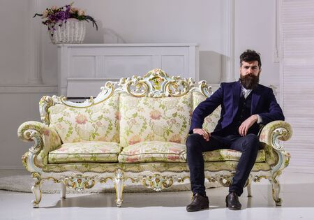 Man with beard and mustache wearing fashionable classic suit, sits on old fashioned couch or sofa. Macho attractive and elegant on serious face and thoughtful expression. Fashion and style concept Foto de archivo