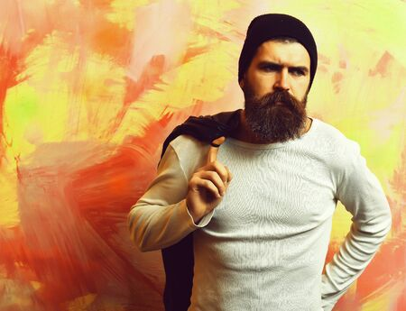 Bearded brutal caucasian hipster with black leather jacket on shoulder