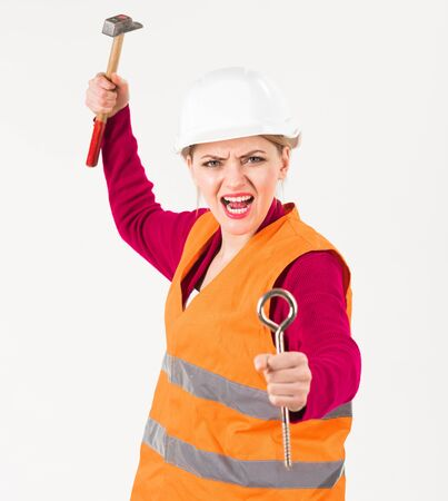 Young woman works with tools as builder.