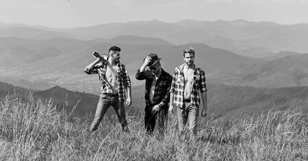 Bring music to life. people spend free time together. hiking adventure. cowboy men. western camping. campfire songs. happy men friends with guitar. friendship. men with guitar in checkered shirt